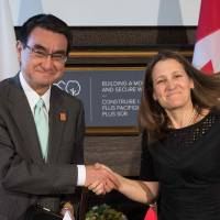 Foreign Minister Taro Kono poses with Canadian counterpart Chrystia Freeland  after they signed a mutual defense supply agreement in Toronto on Saturday. The two agreed to maintain maximum pressure on North Korea to get it to abandon its nuclear and missile programs. | AFP-JIJI