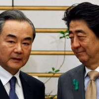 China's top diplomat, Wang Yi, meets with Prime Minister Shinzo Abe during high-level bilateral economic talks in Tokyo on Monday. | REUTERS