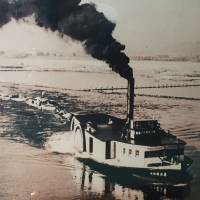 A photo at the Yodogawa Museum in Hirakata, Osaka Prefecture, shows old ships in the late 1800s that brought passengers upriver from Osaka to Kyoto's Fushimi in a journey that could take at least eight hours. Today, a train makes the same journey in about 30 minutes. | ERIC JOHNSTON