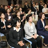 Korean residents who gathered at the Korean Cultural Center in Osaka on Friday applaud as they watch a live broadcast of North Korean leader Kim Jong Un and South Korean President Moon Jae-in shaking hands. | KYODO