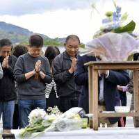 People pray on the second anniversary of the earthquakes that hit Kumamoto Prefecture and surrounding areas in 2016. | KYODO