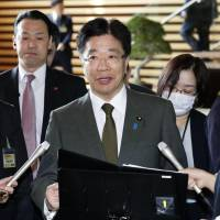 Labor minister Katsunobu Kato speaks to reporters at the Prime Minister's Office on Friday following the Cabinet's approval of a labor reform bill. | KYODO
