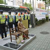 Police stand guard near a statue of a girl symbolizing the issue of wartime 'comfort women' in front of the Japanese Consulate General in Busan, South Korea, on Monday. | KYODO