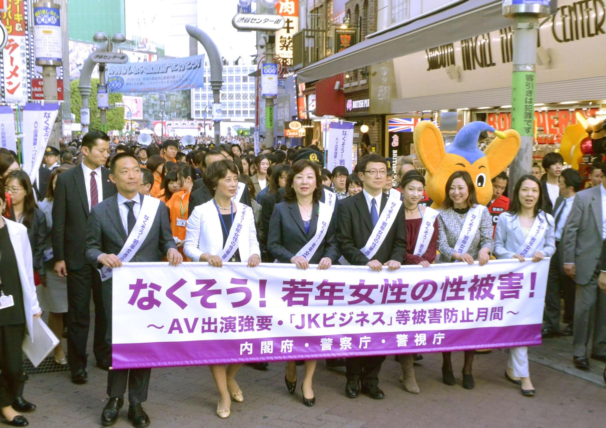 Seiko Noda (center), minister for women's empowerment, marches with senior government officials and police officers along a bustling street in the Shibuya district Friday to call for an end to sex crimes targeting young women. | KYODO