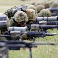 Members of the Ground Self-Defense Force's Amphibious Rapid Deployment Brigade, Japan's first marine unit since World War II, take part in a drill at Camp Ainoura in Sasebo, Nagasaki Prefecture, on Saturday. | REUTERS