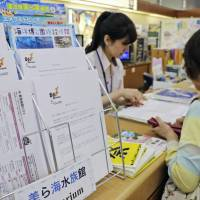 A notice cautioning tourists about measles is seen at a counter at Naha Airport in Okinawa Prefecture on Thursday. | KYODO