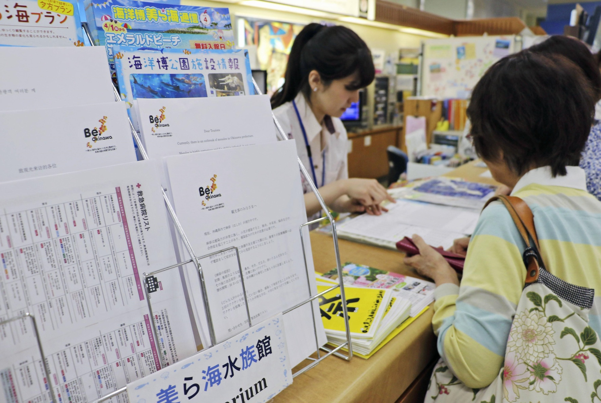 A notice cautioning tourists about measles is seen at a counter at Naha Airport in Okinawa Prefecture on Thursday.   KYODO