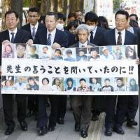 Family members of Okawa Elementary School students and officials killed by tsunami following the March 2011 earthquake walk toward the Sendai High Court on Thursday. | KYODO
