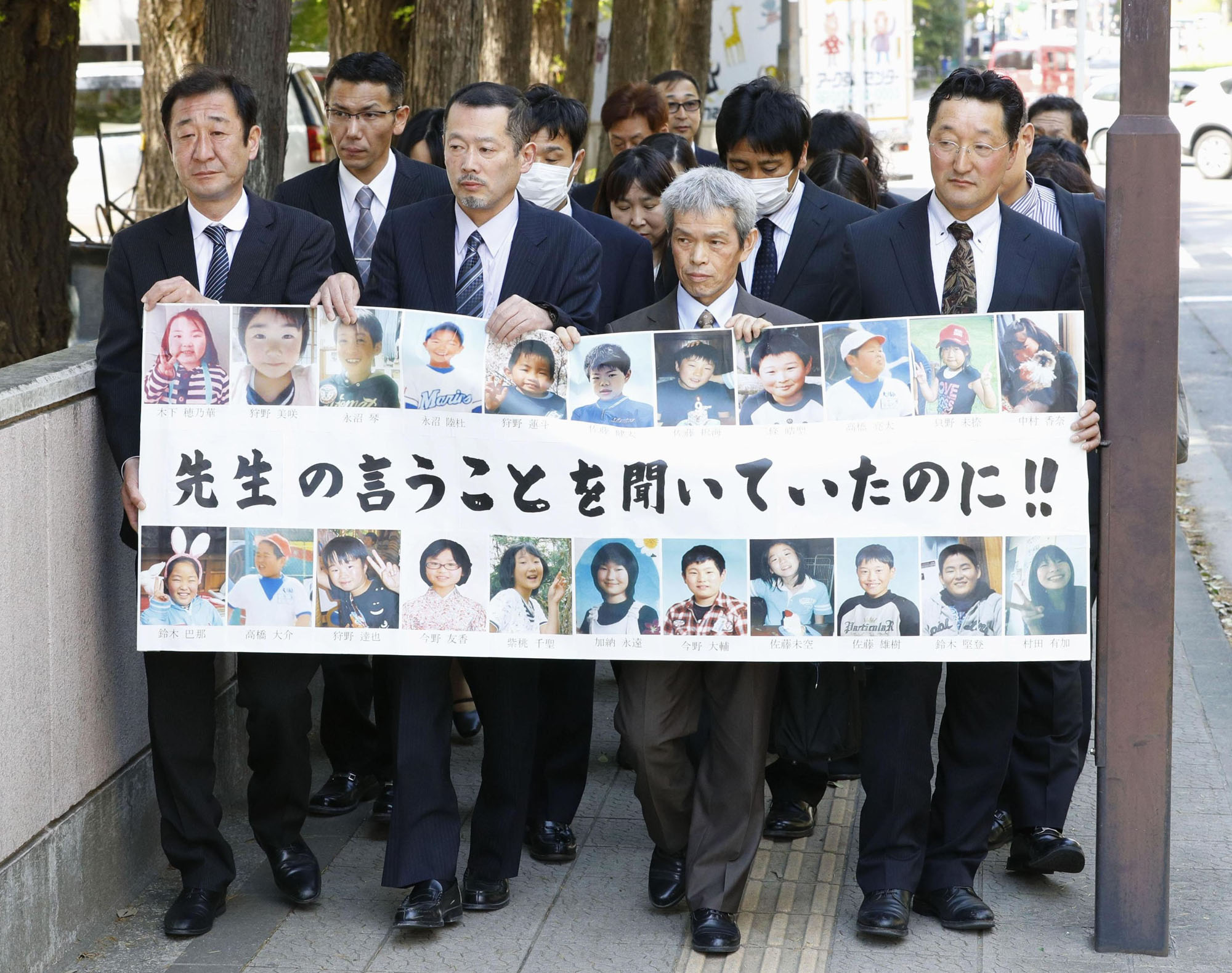 Family members of Okawa Elementary School students and officials killed by tsunami following the March 2011 earthquake walk toward the Sendai High Court on Thursday.   KYODO