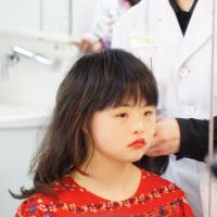 A participant in the Special Beauty Japan pageant checks her makeup while waiting to get her hair done by one of the Yamano Beauty College students who volunteered to help the participants.   MAGDALENA OSUMI