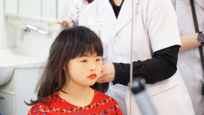 A participant in the Special Beauty Japan pageant checks her makeup while waiting to get her hair done by one of the Yamano Beauty College students who volunteered to help the participants.