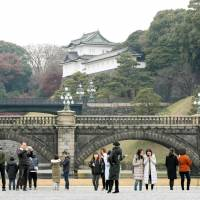 Tourists walk around the Imperial Palace in Tokyo in December 2017. English-speaking guides will be available for tours from the beginning of May. | KYODO