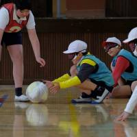 Blindfolded children play goal-ball, a sport for the visually impaired, during a class at a school in suburban Tokyo on Feb. 26. | AFP-JIJI