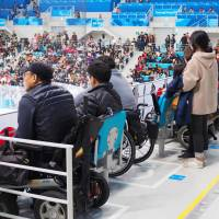 People in wheelchairs watch an ice hockey game during the Pyeongchang Paralympics in South Korea last month. | KYODO