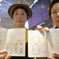 Tourists show off passport stamps after arriving at Narita airport earlier this month. Many airports around the world are abolishing passport stamps and introducing biometric identification instead to speed up immigration procedures amid growing airport congestion. | KYODO
