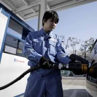 An employee inserts the nozzle of a hydrogen pump into a Toyota Motor Corp. Mirai fuel cell vehicle (FCV) during a demonstration at the Kawasaki Hydrogen Station in Kawasaki in March.   BLOOMBERG