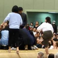 A YouTube screenshot shows women climbing into the dohyō (sumo ring) to assist Maizuru Mayor Ryozo Tatami after he collapsed earlier this month during a spring tournament in Kyoto. | KYODO