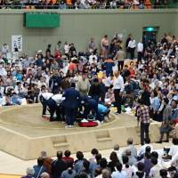 People assist Maizuru Mayor Ryozo Tatami after he collapsed within the dohyō (sumo ring) during a spring tournament in Maizuru, Kyoto Prefecture, on April 4, in this photo provided by a spectator.   KYODO