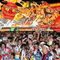 People dance in front of floats at the Nebuta Matsuri in the city of Aomori on Aug. 2.   KYODO