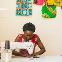 A Ugandan artisan uses a sewing machine at a workshop in Kampala, producing African-print bags for Ricci Everyday. | RICCI EVERYDAY / VIA KYODO