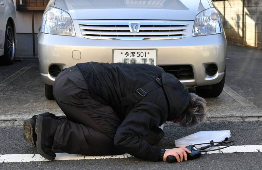 Japan Lost Pet Rescue founder Masataka Endo searches under a car for a missing cat.