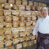 Hiroshi Miyazaki, a priest at Azusamiten Shrine in western Tokyo, shows off wooden plaques that have been placed to aid the return of missing cats. | MAY MASANGKAY