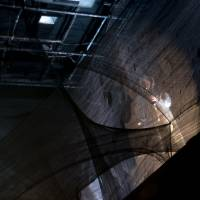 Ghost on the catwalk: A musician plays saxophone while walking a catwalk above the main performance space. | ERIK LUEBS