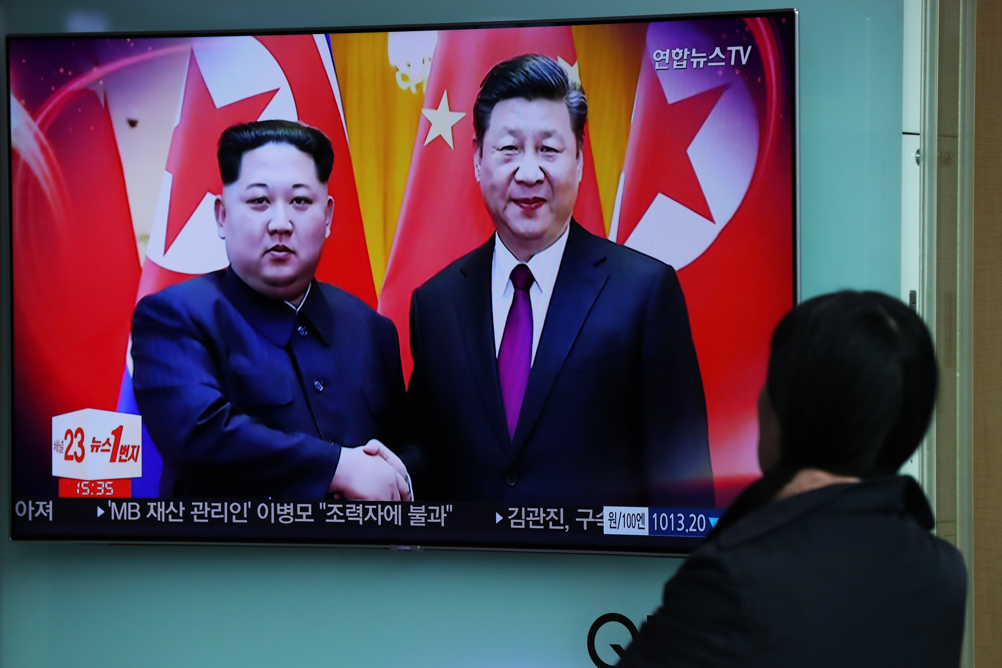 A South Korean woman watches a news broadcast at Seoul Station on March 28 about North Korean leader Kim Jong Un's meeting with Chinese President Xi Jinping. | BLOOMBERG