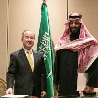 Softbank Group Corp. chairman and CEO Masayoshi Son appears with Saudi Crown Prince Mohammed bin Salman in New York on March 27 after signing a memorandum of understanding  to develop a $200 billion solar power project in the kingdom. | BLOOMBERG