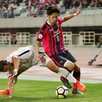 Cerezo Osaka striker Kenyu Sugimoto (9) tries to escape the attentions of a Jeju United defender during his team's 2-1 win over the South Korean team in the Asian Champions League on Tuesday. | KYODO