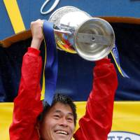 Yuki Kawauchi holds up the trophy after his shocking win in the Boston Marathon on Monday. | REUTERS