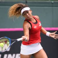 Japan's Naomi Osaka hits a return to Britain's Heather Watson in their Fed Cup World Group II playoff match on Saturday in Miki, Hyogo Prefecture. | AFP-JIJI