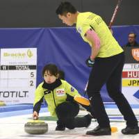 Satsuki Fujisawa launches a stone as teammate Tsuyoshi Yamaguchi watches on Saturday at the World Mixed Doubles Curling Championship in Oestersund, Sweden. | KYODO