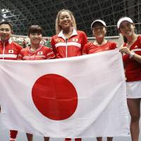 Japan's Fed Cup team celebrates after beating Britain in a playoff to secure a return to the competition's top level on Sunday in Miki, Hyogo Prefecture. | KYODO