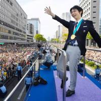 Two-time Olympic gold medalist Yuzuru Hanyu waves to the crowd during a victory parade on Sunday in Sendai. | AFP-JIJI