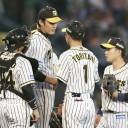 Hanshin's Shintaro Fujinami (center) speaks with the Tigers infielders during a mound visit in the third inning of the team's game against the Giants at Koshien Stadium on Friday.