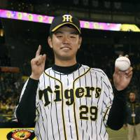 Tigers rookie Haruto Takahashi poses with the winning ball after earning his first NPB victory on Wednesday at Koshien Stadium.   KYODO