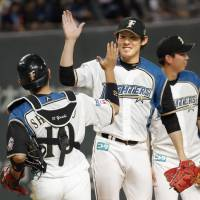 Fighters pitcher Hirotoshi Takanashi (right) celebrates with catcher Yushi Shimizu after Hokkaido Nippon Ham's victory over the Buffaloes on Wednesday in Sapporo. | KYODO
