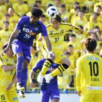 Sanfrecce forward Patric (39) and Reysol midfielder Hajime Hosogai (37) vie for a ball during the first half of their match on Sunday. | KYODO