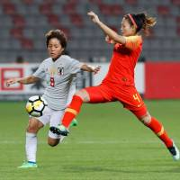 Mana Iwabuchi (left) vies with China's Danyang Li during Japan's 3-1 win on Tuesday in their Women's Asian Cup semifinal in Amman. | AFP-JIJI