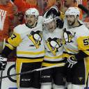 The Penguins' Sidney Crosby (left), Jake Guentzel and Kris Letang celebrate after Guentzel's goal in the third period of their playoff game against the Flyers on Sunday in Philadelphia. The Penguins won 8-5 to clinch the series in six games.