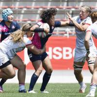 Japan's Chiharu Nakamura (center) takes on the United States' defense during their game on Sunday at the Kitakyushu Sevens. | KYODO