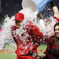 The Angels' Shohei Ohtani is doused with water by teammate Kole Calhoun during a postgame interview on Tuesday in Anaheim, California. | AP