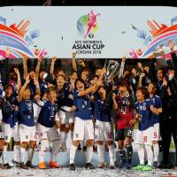 Nadeshiko Japan players and staff celebrate with the trophy after winning the Women's Asian Cup on Friday night with a 1-0 victory over Australia in Amman. | AFP-JIJI
