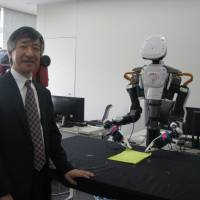 Hideki Asoh, deputy director of the Artificial Intelligence Research Center at the National Institute of Advanced Industrial Science and Technology, shows a robot capable of learning how to fold cloth at its research center in Tokyo on April 11. | KYODO