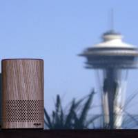 An Amazon Echo device sits on a balcony outside an Amazon office as the Space Needle is reflected in windows behind it following a program announcing several new Amazon products by the company, in Seattle last year. Amazon says an 'unlikely' string of events prompted its Echo personal assistant device to record a Portland, Oregon, family's private conversation and then send the recording to an acquaintance in Seattle. | AP