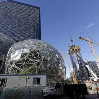 Large spheres take shape in front of an existing Amazon building (behind) as new construction continues across the street in Seattle last October. Amazon said Wednesday it is pausing construction on a new high-rise building in Seattle while it awaits the outcome of a city proposal to tax worker hours. | AP