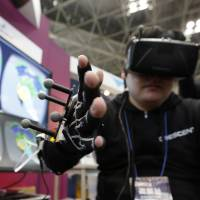 An attendant wearing an Oculus VR Inc. Rift virtual reality headset demonstrates a glove with a Yamaha Corp. rubber-like stretchable strain sensor at the Wearable Expo in Tokyo in January 2016. | BLOOMBERG