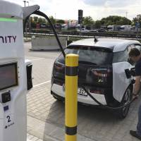 A motorist charges his BMW electric vehicle at the Brohltal Ost rest stop on the A61 motorway in Niederzissen, Germany, on Friday. | AP