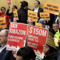 Opponents and supporters of a controversial proposal to tax large businesses such as Amazon.com to fund efforts to combat homelessness hold signs as they attend a Seattle City Council committee meeting at City Hall in Seattle May 9. A divided Seattle City Council is set to decide Monday on the proposal to tax large businesses to fight homelessness. | AP